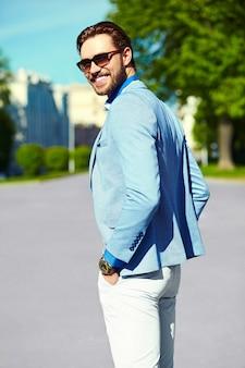 Geschäftsmann im blauen anzug, der sonnenbrille in der straße trägt