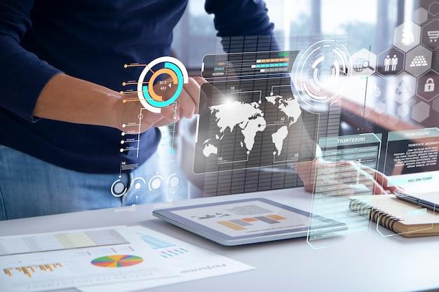 Geschäftsmann im blauen freizeitkostüm, das futuristischen augmented-reality-touchscreen berührt, während geschäftsinformationen auf leistung analysiert werden