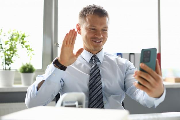 Geschäftsmann im büro, das auf videoanruf auf smartphone spricht. fernarbeitskonzept