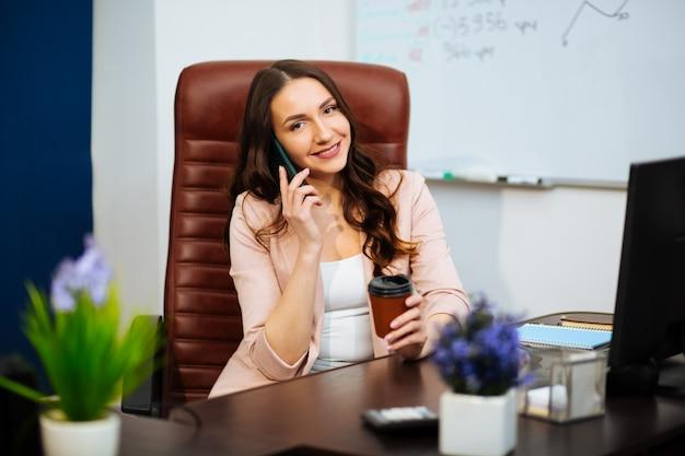 Geschäftsmann im büro, das mit telefon arbeitet