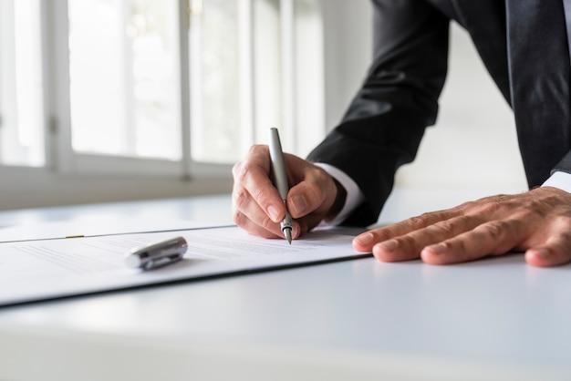 Geschäftsmann im büro, das vertrag unterzeichnet