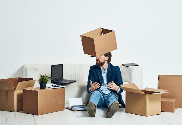 Geschäftsmann im büro, der sachen auspackt, die arbeit bewegen