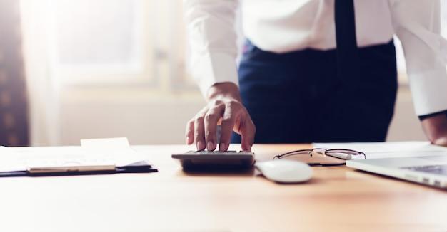 Geschäftsmann im büro und im gebrauch computer und taschenrechner, zum von finanzbuchhaltung durchzuführen