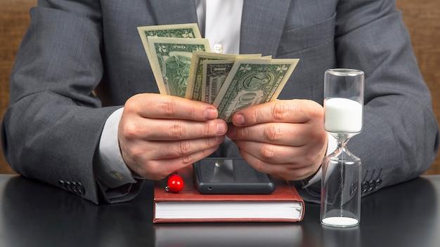 Geschäftsmann im büro zählt geld vor dem hintergrund von sonnenuhren. geschäft und vergütung.