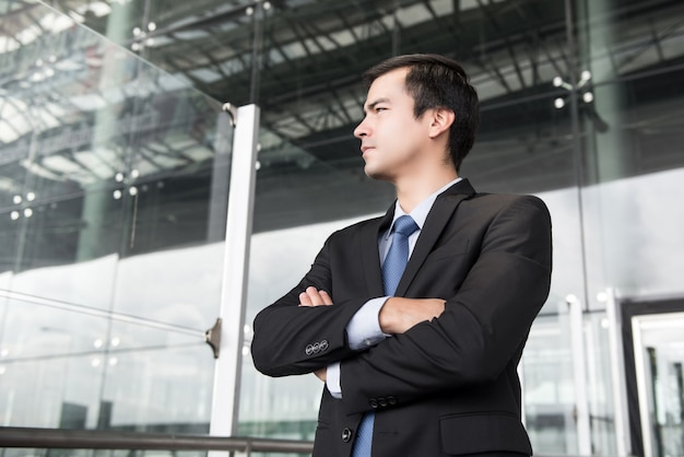 Geschäftsmann im dunkelgrauen anzug, der seine arme kreuzt