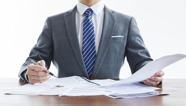 Geschäftsmann im eleganten anzug bei einem geschäftstreffen, das einige dokumente im büro überprüft