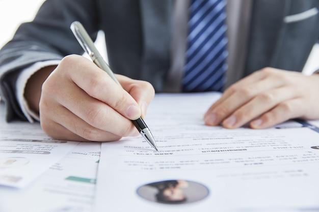 Geschäftsmann im eleganten anzug bei einem geschäftstreffen, das verträge im büro unterschreibt