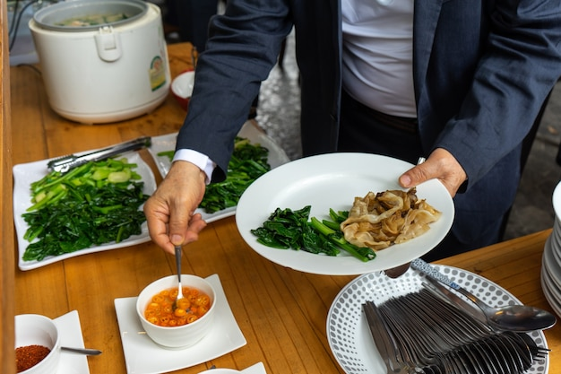 Geschäftsmann im geschäftsanzug, der die gebratene nudel mit schweinefleisch und brokkoli zum mittagessen vorbereitet.