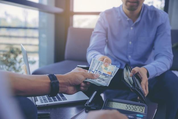Geschäftsmann im geschäftstreffen, das nach verhandlungen mit geschäftspartnern zählt und geld bezahlt
