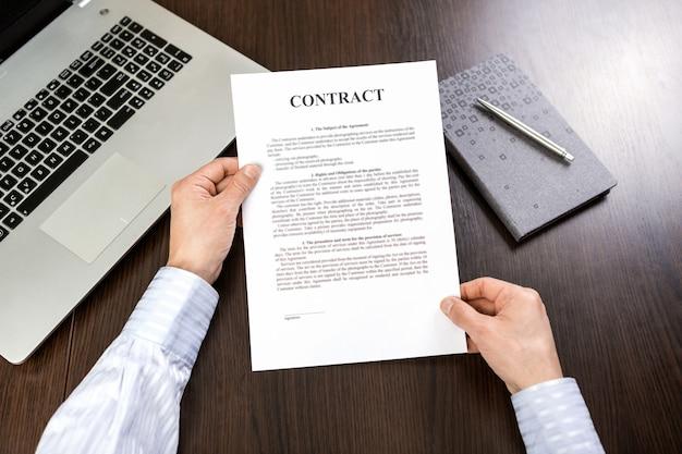 Geschäftsmann im hemd, das vertragsdokumente am schreibtisch im büro liest. laptop und planung mit stift auf dem tisch.