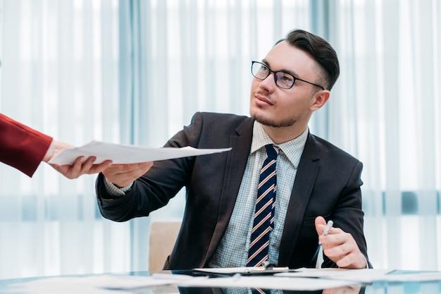 Geschäftsmann im intelligenten anzug, der im büro arbeitet