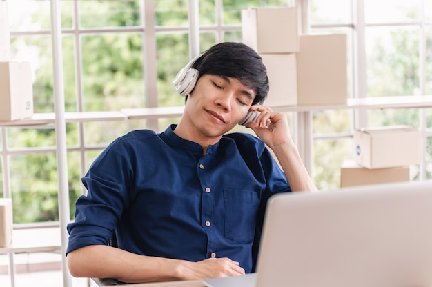 Geschäftsmann im kopfhörer, der musik im büro hört
