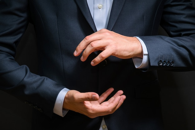 Geschäftsmann im luxuriösen blauen anzug stellt neues produkt auf dunkelheit vor