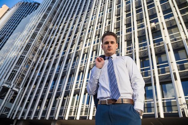 Geschäftsmann im noblen anzug, der seine jacke auf hintergrund des modernen bürowolkenkratzers hält.