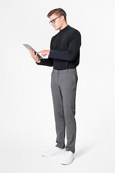 Geschäftsmann im rollkragenpullover arbeitet an tablet-ganzkörperaufnahme