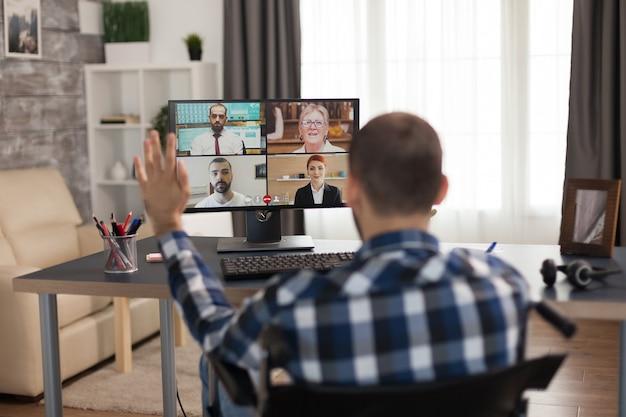Geschäftsmann im rollstuhl winkt während eines videoanrufs mit geschäftspartnern. junger immobilisierter freiberufler, der sein geschäft online macht, high-tech verwendet, in seiner wohnung sitzt und aus der ferne arbeitet