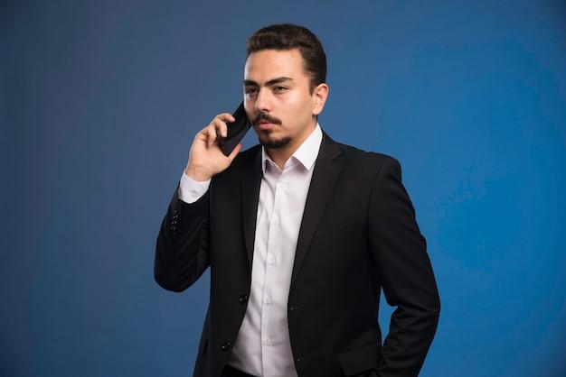 Geschäftsmann im schwarzen anzug, der mit dem telefon spricht.