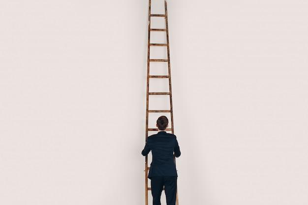 Geschäftsmann im schwarzen anzug die treppe hochheben. karriere und wachstum im geschäftskonzept.