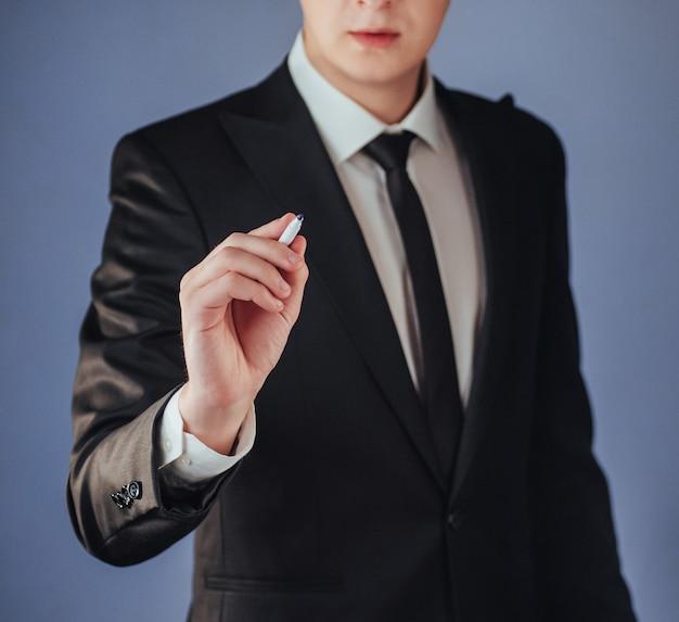 Geschäftsmann im schwarzen anzug etwas an bord mit markierung zu schreiben