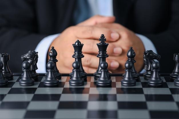 Geschäftsmann im schwarzen anzug sitzend und kontrollteam vor zur erfolgsposition auf wettbewerbsgeschäftsspiel