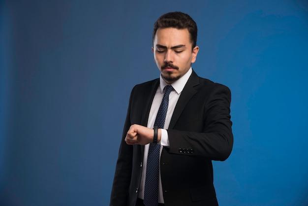 Geschäftsmann im schwarzen anzug überprüft seine zeit.
