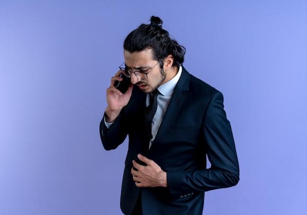 Geschäftsmann im schwarzen anzug und in den gläsern, die auf handy sprechen, der verwirrt steht, der über blaue wand steht