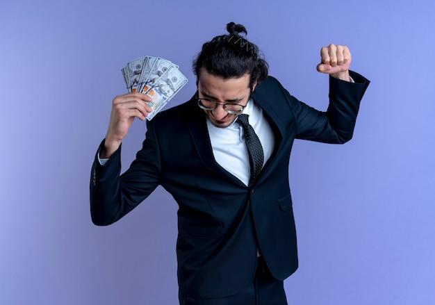 Geschäftsmann im schwarzen anzug und in den gläsern, die bargeld glücklich und aufgeregt halten, geballte faust, die über blaue wand steht
