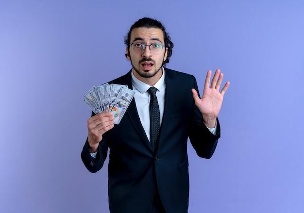Geschäftsmann im schwarzen anzug und in den gläsern, die bargeld halten, das nach vorne schaut, verwirrt mit erhabener hand, die über blauer wand steht