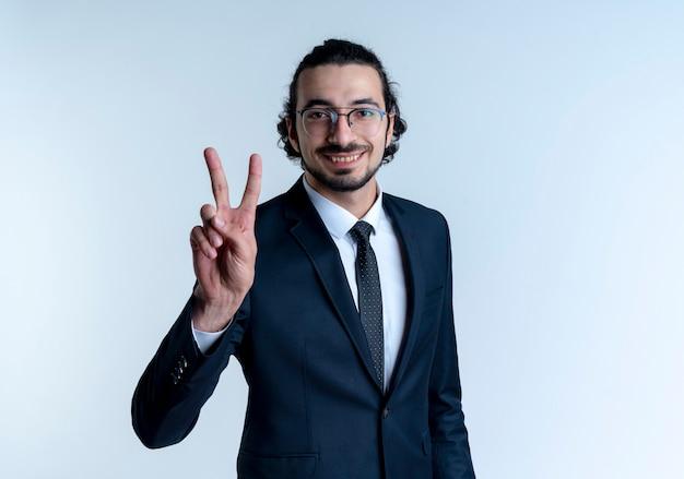 Geschäftsmann im schwarzen anzug und in den gläsern, die das siegeszeichen zeigen, das fröhlich über weißer wand stehend lächelt