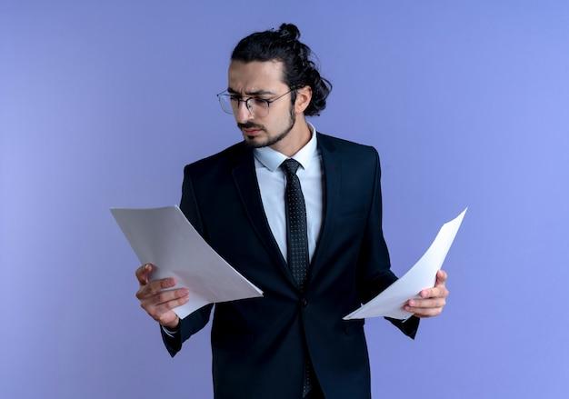 Geschäftsmann im schwarzen anzug und in den gläsern, die dokumente mit ernstem gesicht betrachten, das über blauer wand steht