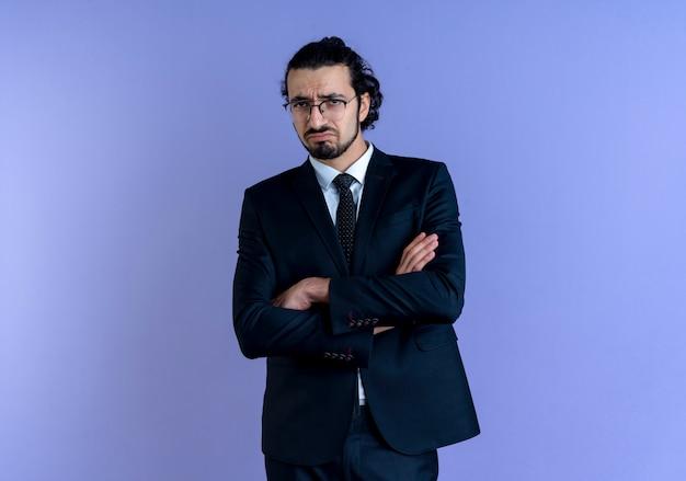 Geschäftsmann im schwarzen anzug und in den gläsern, die nach vorne mit traurigem ausdruck auf gesicht stehen, das über blauer wand steht