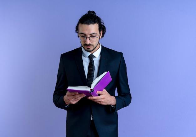 Geschäftsmann im schwarzen anzug und in den gläsern, die notizbuch halten, das es mit ernstem gesicht betrachtet, das über blauer wand 2 steht