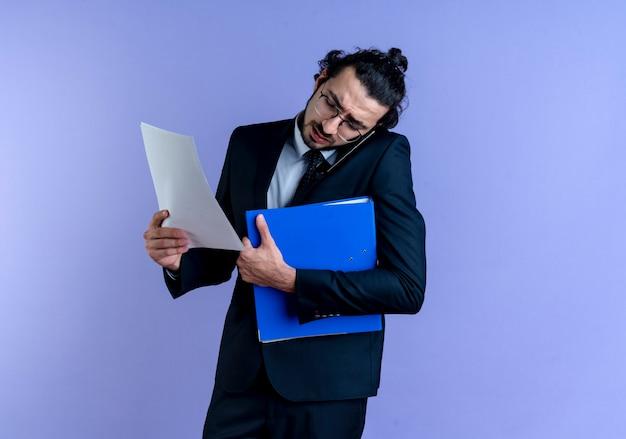 Geschäftsmann im schwarzen anzug und in den gläsern, die ordner und dokumente halten, während auf handy sprechen, das über blaue wand steht