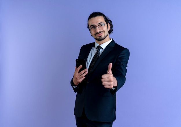 Geschäftsmann im schwarzen anzug und in den gläsern, die smartphone halten daumen zeigen, die zuversichtlich lächeln, über blauer wand stehend