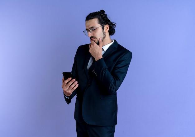 Geschäftsmann im schwarzen anzug und in der brille, die bildschirm seines handys mit nachdenklichem ausdruck auf gesicht betrachten, das über blauer wand steht
