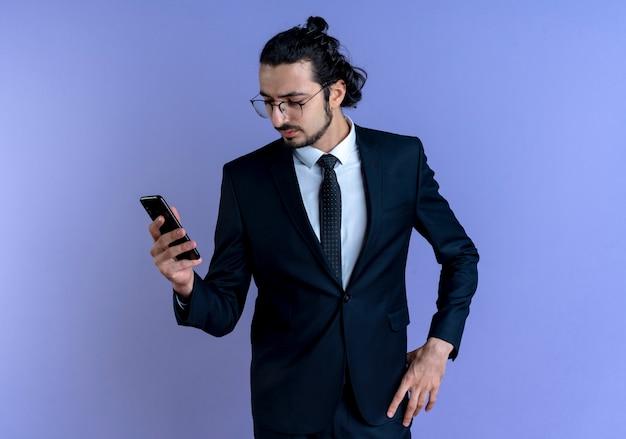 Geschäftsmann im schwarzen anzug und in der brille, die bildschirm seines smartphones mit ernstem gesicht betrachten, das über blauer wand steht