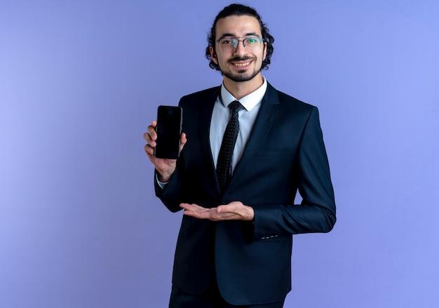 Geschäftsmann im schwarzen anzug und in der brille, die das smartphone zeigt, das es mit arm seiner hand präsentiert, der zuversichtlich über der blauen wand steht