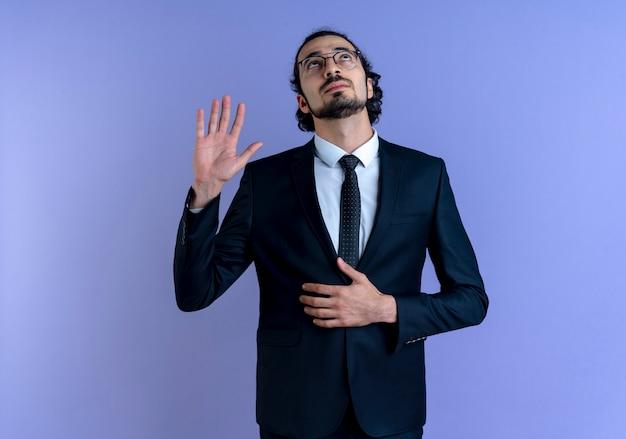 Geschäftsmann im schwarzen anzug und in der brille, die einen eid leisten, der mit ernstem gesicht steht, das über blauer wand steht