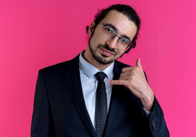 Geschäftsmann im schwarzen anzug und in der brille, die mich geste mit der hand lächelnd selbstbewusst stehend über rosa wand nennen