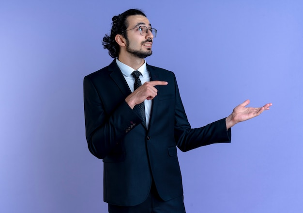 Geschäftsmann im schwarzen anzug und in der brille, die mit arm seiner hand präsentieren, die mit dem finger zur seite zeigt, die zuversichtlich steht, über der blauen wand zu stehen
