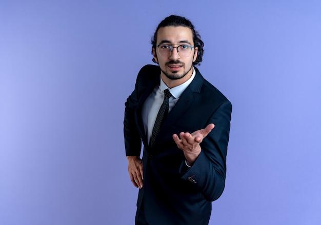 Geschäftsmann im schwarzen anzug und in der brille, die mit ausgestrecktem arm nach vorne schauen, als eine frage stellen, die über blauer wand steht