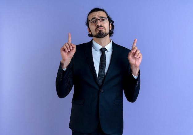Geschäftsmann im schwarzen anzug und in der brille, die mit zeigefingern nach oben zeigt, mit traurigem ausdruck, der über blauer wand steht, nach vorne schaut