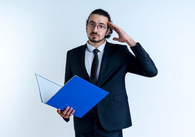 Geschäftsmann im schwarzen anzug und in der brille, die ordner hält, der nach vorne mit dem selbstbewussten ausdruck grüßt, der über weißer wand steht