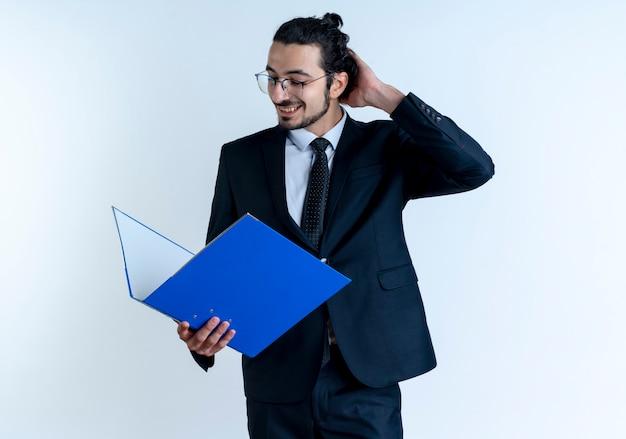 Geschäftsmann im schwarzen anzug und in der brille, die ordner hält, der verwirrt schaut und seinen kopf kratzt, der über weißer wand steht