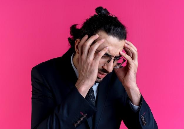 Geschäftsmann im schwarzen anzug und in der brille, die seinen kopf mit den händen halten, die unter starken kopfschmerzen leiden, die über rosa wand stehen