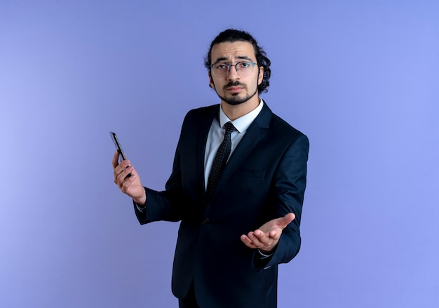 Geschäftsmann im schwarzen anzug und in der brille, die smartphone halten, das mit arm heraus nach vorne schaut, als fragend, über blauer wand stehend