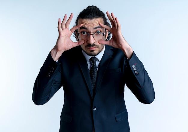 Geschäftsmann im schwarzen anzug und in der brille, die versuchen, die augen mit den fingern, die über der weißen wand stehen, weiter zu öffnen