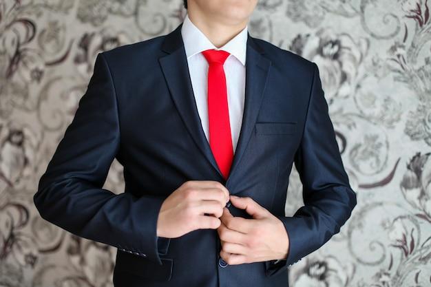 Geschäftsmann im schwarzen anzug und in einer roten krawatte.