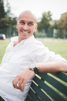 Geschäftsmann im weißen hemd, das auf einer bank in einem park sitzt