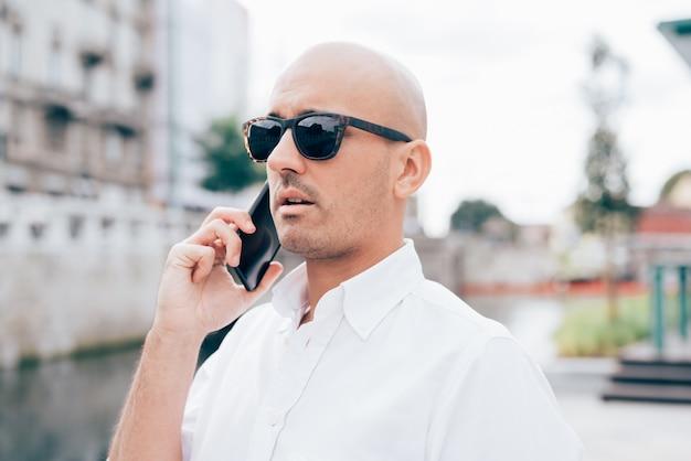 Geschäftsmann im weißen hemd mit der schwarzen sonnenbrille, die am telefon spricht